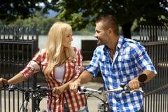 Pares casuales felices con la bicicleta en parque al aire libre Foto de archivo libre de regalías