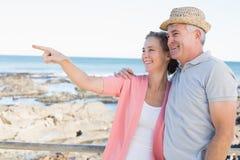 Pares casuales felices que miran algo por la costa Imagen de archivo libre de regalías