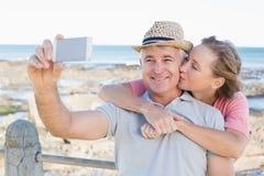 Pares casuales felices que toman un selfie por la costa Foto de archivo