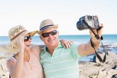 Pares casuales felices que toman un selfie por la costa Imagen de archivo libre de regalías