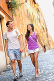 Pares casuales jovenes que celebran caminar de las manos Imagen de archivo