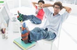 Pares casuales relajados con las piernas en el escritorio en oficina Foto de archivo libre de regalías