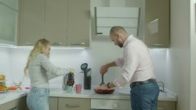 Pares casuales románticos que hacen el desayuno en cocina metrajes