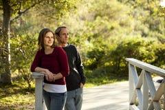 Pares caucásicos en amor en el puente de madera al aire libre Foto de archivo libre de regalías