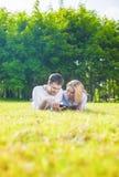 Pares caucásicos felices en el amor que miente en la hierba al aire libre leído Foto de archivo libre de regalías