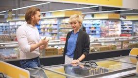Pares caucásicos felices que eligen la comida congelada en el colmado en alameda de compras almacen de metraje de vídeo