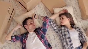 Pares caucásicos felices que mienten en el piso en un nuevo apartamento entre las cajas metrajes