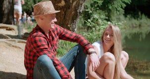 Pares caucásicos hermosos que se relajan en un bosque durante día soleado Imágenes de archivo libres de regalías