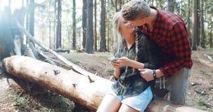 Pares caucásicos jovenes cariñosos usando el teléfono en un bosque Imagen de archivo