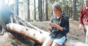 Pares caucásicos jovenes cariñosos usando el teléfono en un bosque Fotos de archivo