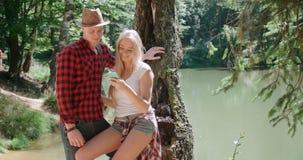 Pares caucásicos jovenes cariñosos usando el teléfono por un lago Fotos de archivo libres de regalías
