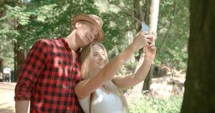 Pares caucásicos jovenes cariñosos usando el teléfono por un lago Foto de archivo