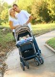 Pares caucásicos jovenes felices con el bebé en parque imagen de archivo libre de regalías