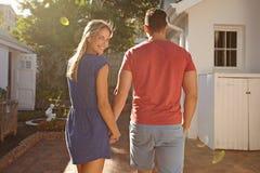 Pares caucásicos jovenes que caminan en el patio trasero Foto de archivo libre de regalías