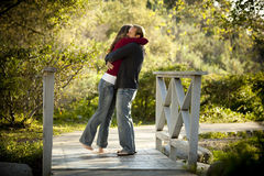 Pares caucásicos que abrazan en el puente de madera al aire libre Imagen de archivo libre de regalías