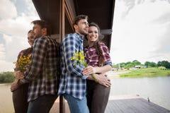 Pares caucásicos que abrazan mientras que se coloca cerca de la ventana al aire libre Imagen de archivo libre de regalías
