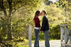 Pares caucásicos que se besan en el puente de madera al aire libre Imágenes de archivo libres de regalías