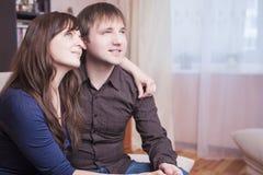 Pares caucásicos que se sientan junto abrazado Mirada hacia arriba Fotos de archivo