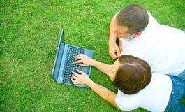 Pares caucásicos usando la computadora portátil al aire libre Fotos de archivo libres de regalías