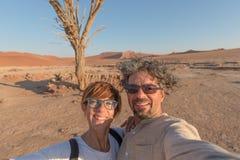 Pares caucasianos adultos que tomam o selfie em Sossusvlei no deserto de Namib, parque nacional de Namib Naukluft, destino princi fotografia de stock