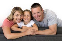 Pares caucasianos bonitos e felizes novos com o levantamento da mãe e do pai alegre junto com 7 anos adoráveis pequeno louro velh Fotos de Stock Royalty Free