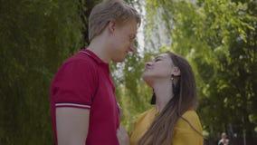 Pares caucasianos bonitos no amor maciamente que abraça e que sorri no fundo do parque verde da mola Data de novo filme