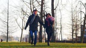 Pares caucasianos felizes novos românticos que têm o divertimento no parque