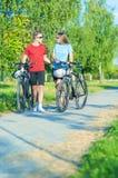 Pares caucasianos felizes que andam com as bicicletas na natureza Surroundi imagens de stock royalty free