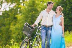 Pares caucasianos felizes que andam na área do parque com bicicleta Imagens de Stock Royalty Free