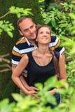 Pares caucasianos loving felizes novos que abraçam e que sonham na floresta do verão imagem de stock royalty free