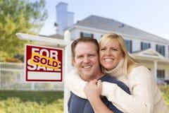 Pares caucasianos na frente da casa nova e do sinal vendido Fotos de Stock Royalty Free