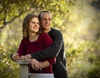 Pares caucasianos no amor na ponte de madeira ao ar livre Fotografia de Stock Royalty Free