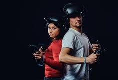 Pares caucasianos novos com auriculares e controladores de VR imagens de stock