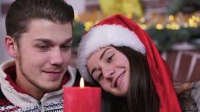 Pares caucasianos novos do close-up que sorriem e que olham em uma vela ardente vermelha vídeos de arquivo