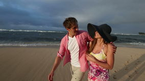 Pares caucasianos novos loving que guardam as mãos que andam junto praia Oahu Havaí filme