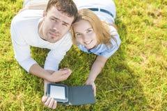 Pares caucasianos novos no amor que encontra-se fora na grama e no Havin Fotos de Stock