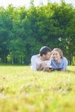 Pares caucasianos novos no amor que encontra-se fora na grama e no Havin Imagens de Stock