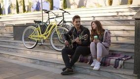 Pares caucasianos novos que sentam-se nas escadas e no homem que jogam a guitarra ao sentar-se com sua amiga fora no filme