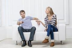 Pares caucasianos novos que sentam-se no sofá imagens de stock royalty free