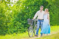 Pares caucasianos novos que têm uma caminhada no parque com bicicleta Fotografia de Stock