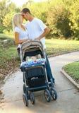 Pares caucasianos novos que tomam seu bebê na caminhada fotografia de stock