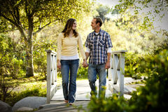 Pares caucasianos que andam na ponte de madeira ao ar livre Imagem de Stock Royalty Free