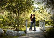 Pares caucasianos que beijam na ponte de madeira ao ar livre Fotos de Stock Royalty Free
