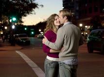 Pares caucasianos que beijam na rua Fotografia de Stock