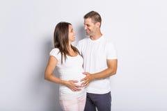 Pares caucasianos que esperam o sorriso do bebê alegre no branco Imagem de Stock
