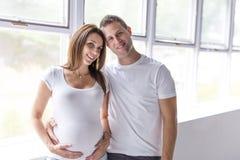 Pares caucasianos que esperam o sorriso do bebê alegre no branco Fotografia de Stock Royalty Free