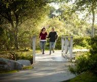 Pares caucasianos que funcionam na ponte de madeira ao ar livre Fotografia de Stock Royalty Free