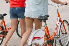 Pares caucasianos que guardam a bicicleta ao andar no pavimento imagens de stock royalty free