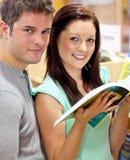 Pares caucasianos que procuram um livro Fotografia de Stock