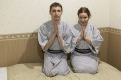 Pares caucásicos jovenes que se sientan en trajes tradicionales en hotel japonés Imagenes de archivo